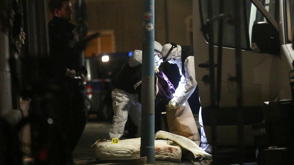 Polizisten der Spurensicherung untersuchen in Herne vor dem Haus, in dem es einen Wohnungsbrand gegeben hatte, eine Matratze.