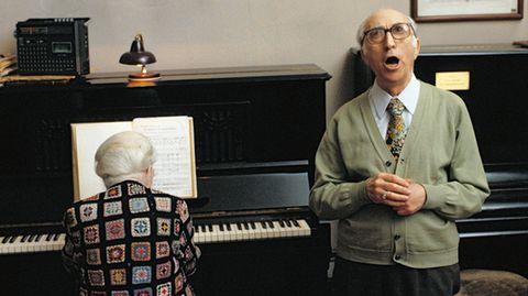 Eine alte Dame am Klavier, ein alter Herr singt. Über dem Klavier hängt eine Inschrift.