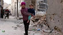 Ein Mädchen in Syrien trägt ihren kleinen Bruder auf dem Arm