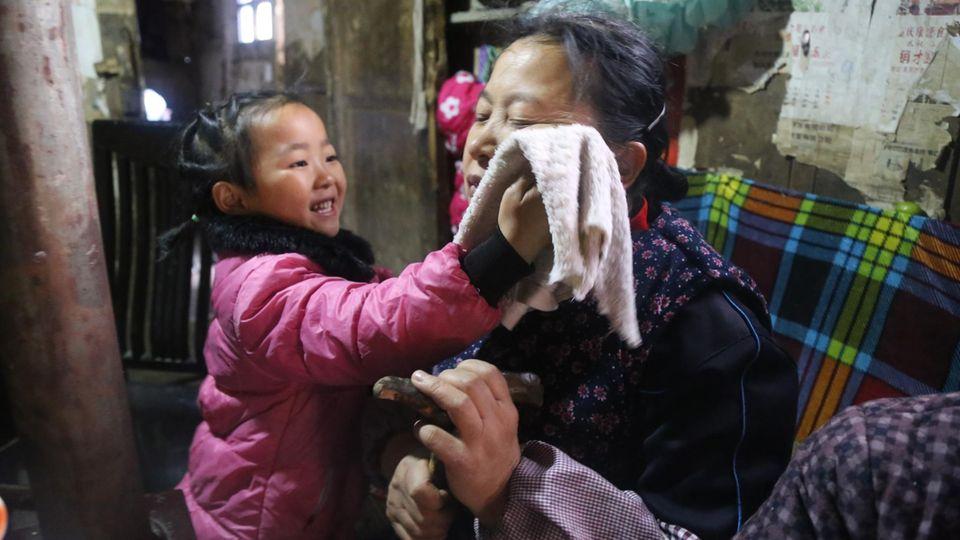 Anna wäscht das Gesicht ihrer Großmutter