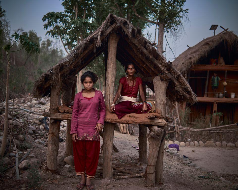 """Der Fotograf Poulomi Basu hat Frauen aufgesucht, die sich im Menstruations-Exil befinden. So will es die """"Chaupadi""""-Tradition. Erst wenn die Monatsblutung abklingt, dürfen die Frauen zu ihren Familien zurückkehren. In der Zwischenzeit schlafen sie oft unter freiem Himmel oder einfachen Hütten wie dieser.  Ranga Hoshi (42, rechts) teilt ihre Unterkunft mit Minu, 14. Dem Fotografen erzählte sie: """"Beim ersten Mal bekam ich Fieber. Ich fühlte mich sehr unwohl. Manchmal bekomme ich Essen, manchmal muss ich hungern. Männer verstehen nicht, was eine Menstruation ist. Wie auch? Mit ihren Körpern passiert das nicht."""" Abgeschnitten von jeder medizinischen Versorgung müssen die Frauen warten. Von ihren Mitmenschen werden sie gemieden."""