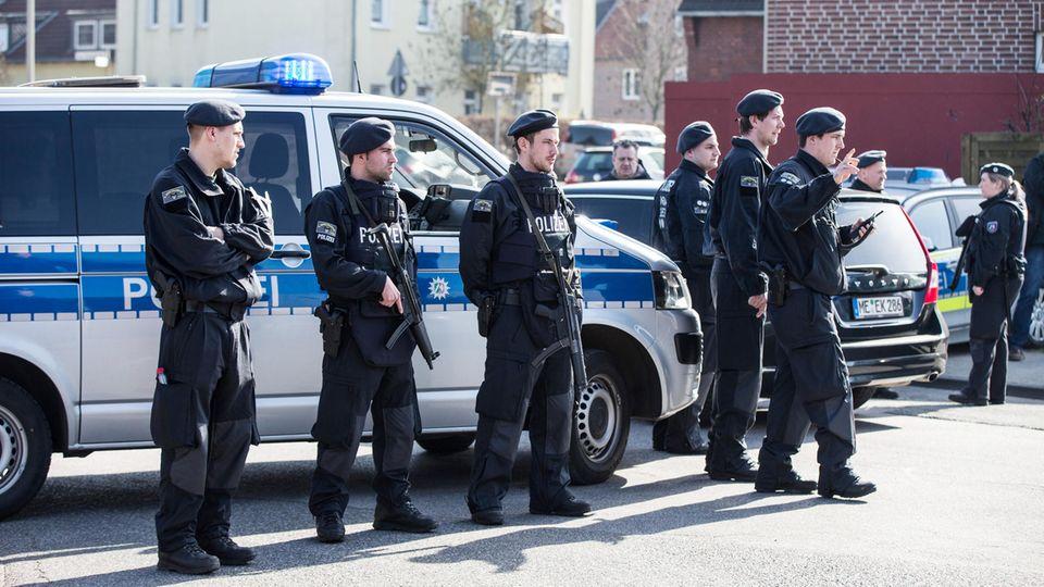Die Polizei sperrt in Duisburg eine Straße, in der eine Bank überfallen wurde