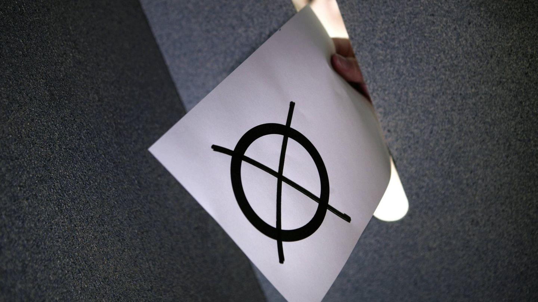 Ein Wahlzettel wird in eine Urne gesteckt (Symbolbild)