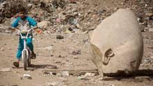 Ein Kind auf dem Fahrrad neben einem Teil des Kopfes eines Pharao-Statue
