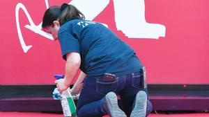 Eine Frau kniet bei der Berlinale auf dem Boden und reinigt einen Vorsprung
