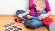 Ein kleiner Junge und seine Mutter betrachten Ultraschallfotos