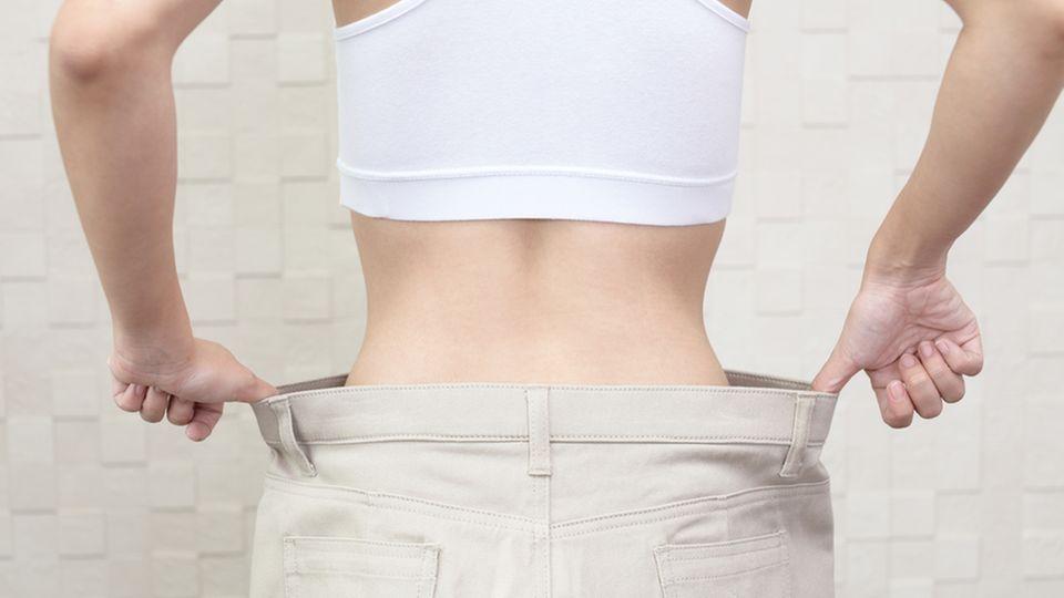 Frau trägt eine viel zu weite Hose und hält sie an den Seiten fest