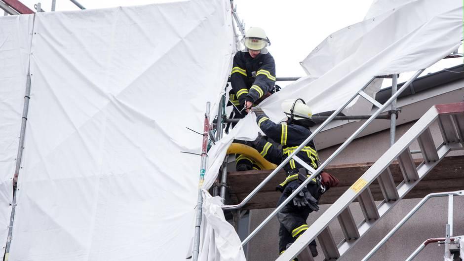 Feuerwehrleute sichern in Hamburg an einem Mehrfamilienhaus Planen an einem Gerüst, die sich durch starken Sturm gelöst haben