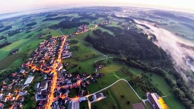 """In der Dämmerung im Ballonflug über dem Kanton St. Gallen: Das Zeitraffer-Video """"Helvetia by Night 360°"""" zeigt die Schweiz im Zwielicht von oben."""