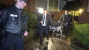 Mitarbeiter eines Bestattungsunternehmens sowie ein Polizist bewegen sich in Hamburg vor einem Mehrfamilienhaus.