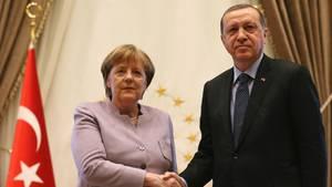 Handshake zwischen Angela Merkel und Recep Tayyip Erdogan - links die türkische Flagge