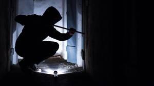 Ein fiktiver Einbrecher versucht mit einem Brecheisen eine Tür aufzuhebeln. Einbruchschutz wird nun staatlich stärker gefördert.