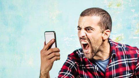 Ein Mann schaut wütend sein iPhone an