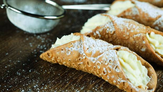 Cannoli  Cannolo ist ein gefülltes Gebäck, das aus Sizilien stammt. Meist besteht es aus einer frittierten Teigrolle mit einer süßen cremigen Füllung aus Ricotta. Die ist entweder mit Vanille, Kakao, Schokostückchen oder kandierten Früchten verfeinert.