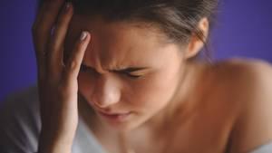 Eine junge Frau hat Kopfschmerzen.