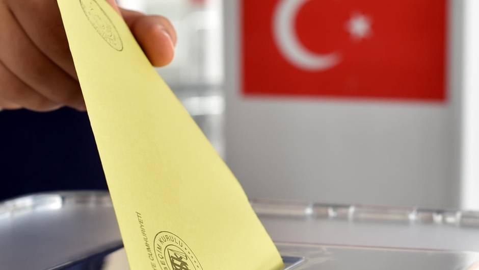 Wahlschein wird in Urne gesteckt (Symbolbild)