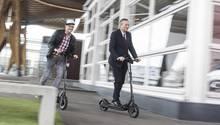 """Vodafone-Chef Hannes Ametsreiter (r.) und Start-up-Gründer Florian Walberg fahren mit dem """"Egrit""""-Roller auf der Cebit-Messe"""