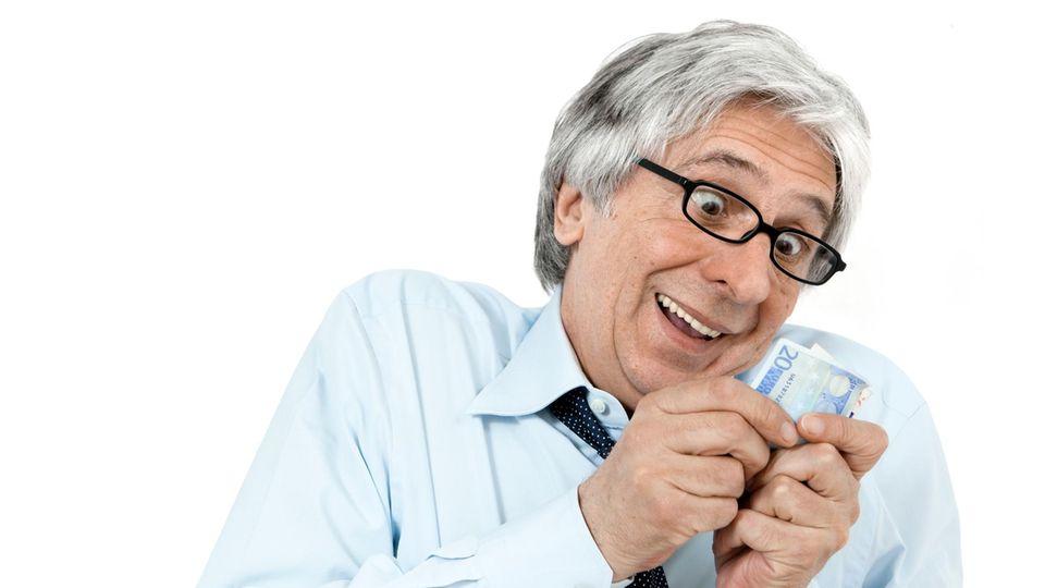 Ein Manns schaut freudig auf einen Geldschein