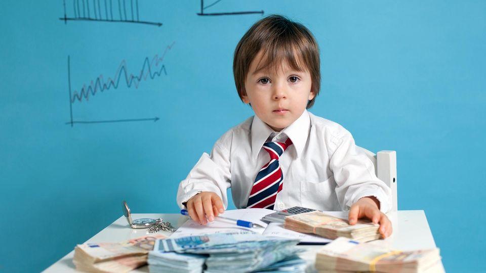 Ein Kind in Hemd und Krawatte spielt mit Geldscheinen
