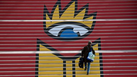 Eine Frau steigt eine Treppe hoch, auf der das Logo der Leipziger Buchmesse zu sehen ist: Ein geöffnetes Buch unter einem Auge.