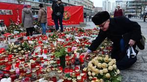 Nach dem Anschlag in Berlin stellt ein Mann eine Kerze auf den Weihnachtsmarkt am Breitscheidplatz