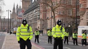 Während der Schweigeminute für die Opfer des Anschlags von London stehen Polizisten mit gesenkten Köpfen still