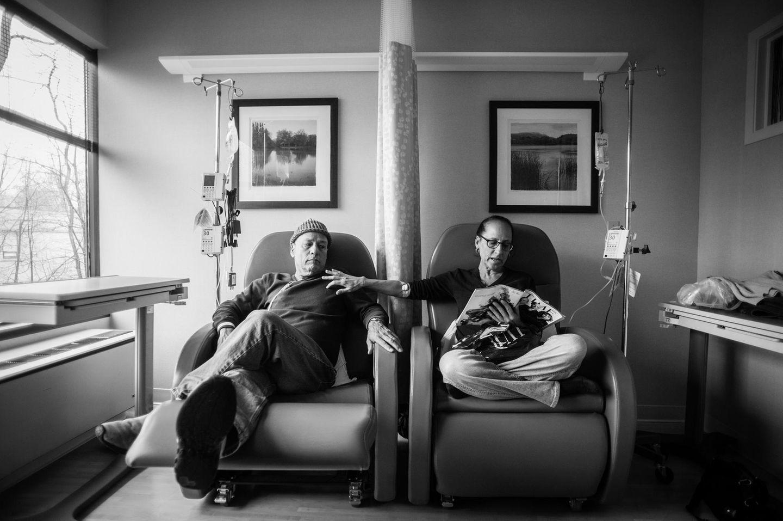 Die Eltern sitzen nebeneinander, währen die Mutter ihre Chemo bekommt