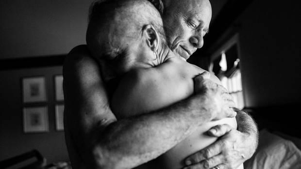 Die Eltern umarmen sich mit blankem Oberkörper