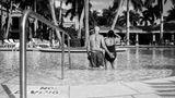 Die Eltern stehen im Swimmingpool mit dem Rücken zur Kamera