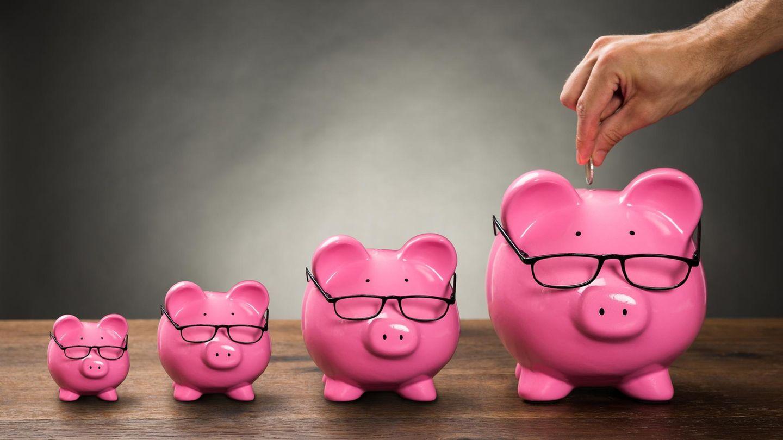 Eine Hand steckt eine Münze in ein rosa Sparschwein