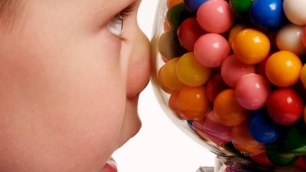 Ein junge drücke sich die Nase an einem Automaten mit großen, bunten Kaugummi-Kugeln platt