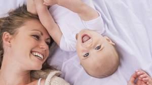 Eine junge Mutter liegt mit einem Baby im Bett (Symbolbild)