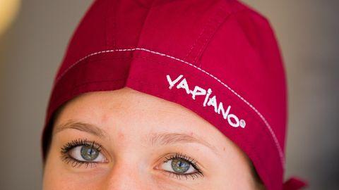 """Eine Frau trägt in einem Restaurant von Vapiano in Bonn (Nordrhein-Westfalen) eine Mütze mit der Aufschrift """"Vapiano""""."""