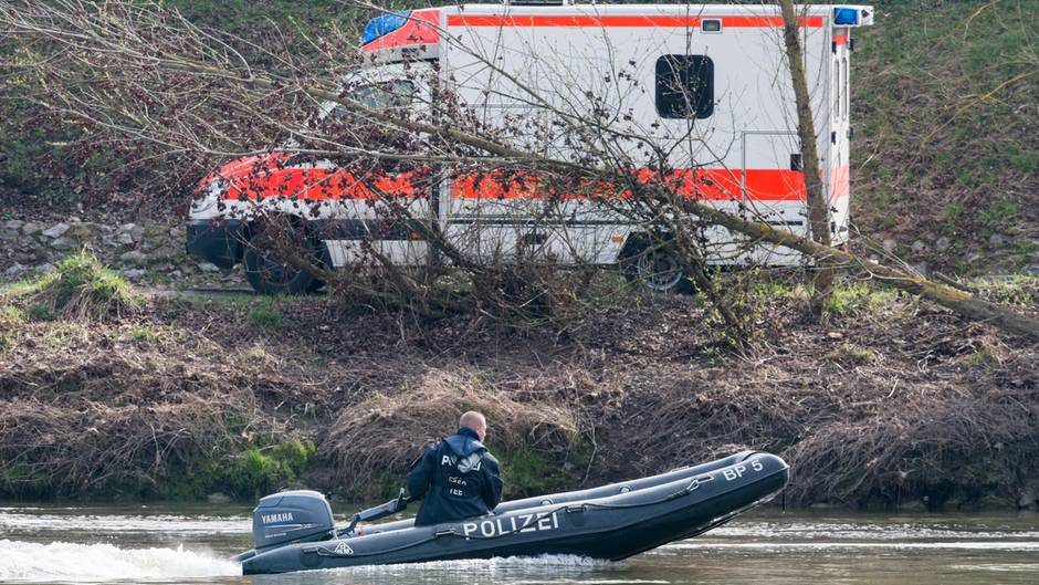 Ein Schlauchboot der Polizei auf der Donau, am Ufer steht ein Rettungswagen