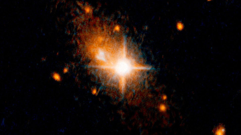 """Die Aufnahme des """"Hubble""""-Weltraumteleskop zeigt denhellen Quasar (Bildmitte).Quasare sind normalerweise die Kerne aktiver Galaxien. Sie werden von einem zentralen Schwarzen Loch angetrieben. Die Schwarzen Löcher selbst lassen sich nicht beobachten, aber die Quasare strahlen meist heller als eine ganze Galaxie."""