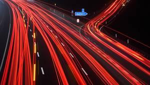 Durch Langzeitbelichtung werden die Schweinwerfer auf einer Autobahn zu Leuchtspuren