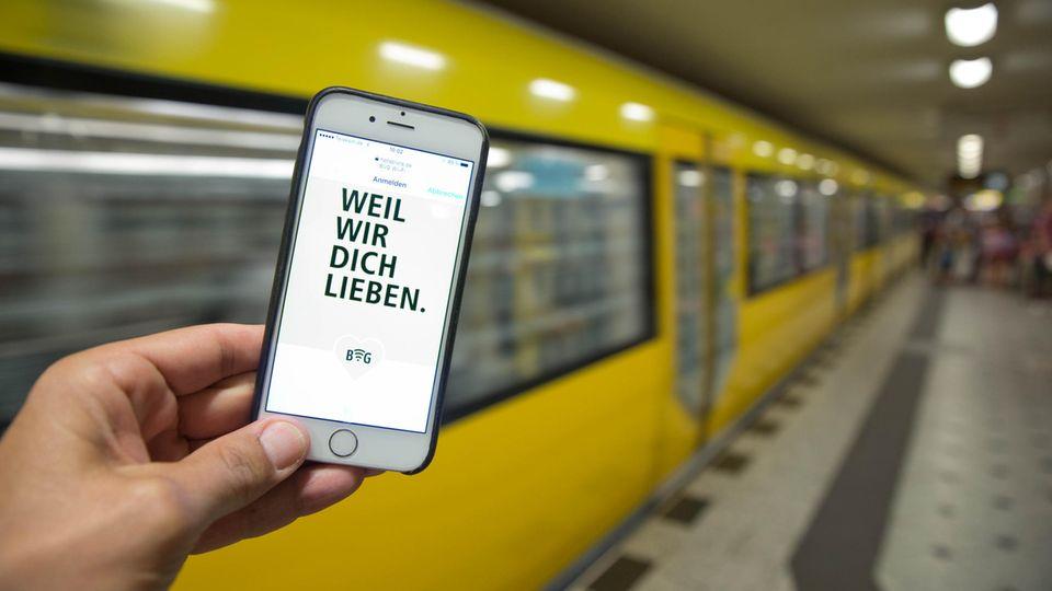 """Ein Smartphone mit dem Schriftzug """"Weil wir dich lieben"""" vor einer gelben Berliner U-Bahn"""