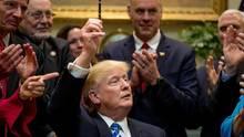 Donald Trump hält im Weißen Haus einen Stift hoch, nachdem er verschiedene Dekrete unterzeichnete