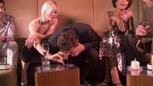 Zu sehen sind einige junge Leute in einem Nachtclub. Ein Mann in der Mitte des Bildes schnieft Kokain durch die Nase.