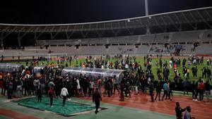 Zu sehen ist die Rasenfläche des Stadions, auf der Dutzende Menschen stehen.