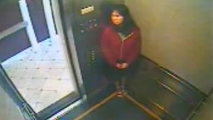 Die dunkelhaarige Elisa L., eine Frau mit roter Jacke in einem Fahrstuhl.