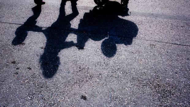 Der Schatten einer Frau, die einen Kinderwagen schiebt und von einem Kleinkind begleitet wird (Symbolbild)