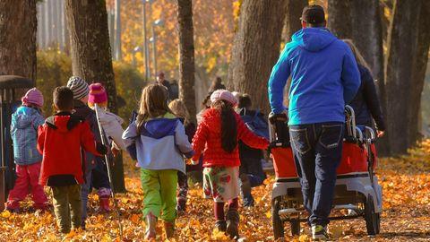 Kinder gehen mit Erwachsenen spazieren (Symbolbild)