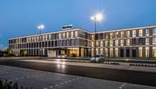 """Ein Verwaltungsgebäude der """"Bünting AG"""" aus Leer in der Abenddämmerung."""