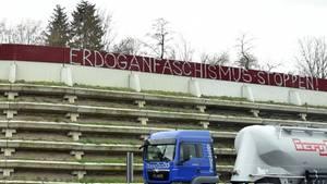 """Der Schriftzug """"Erdoganfaschismus stoppen!"""" an einer Lärmschutzwand einer Autobahn, davor ein vorbeifahrender Sattelschlepper."""