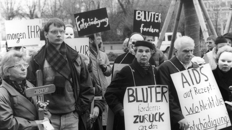 """Zu sehen ist eine Demo mit mehreren Menschen, die Schilder emporstrecken, auf denen beispielsweise """"Entschädigung"""" steht."""