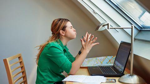 Eine Frau sitzt frustriert vor ihrem alten, dicken Notebook