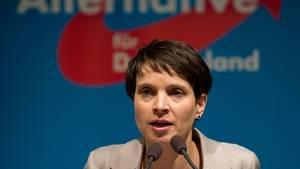 """AfD-Sprecherin Frauke Petry auf einem Podium. Dahinter das Logo der Partei """"Alternative für Deutschland."""""""