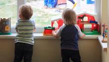 Zwei Kinder schauen aus dem Fenster einer Kita.