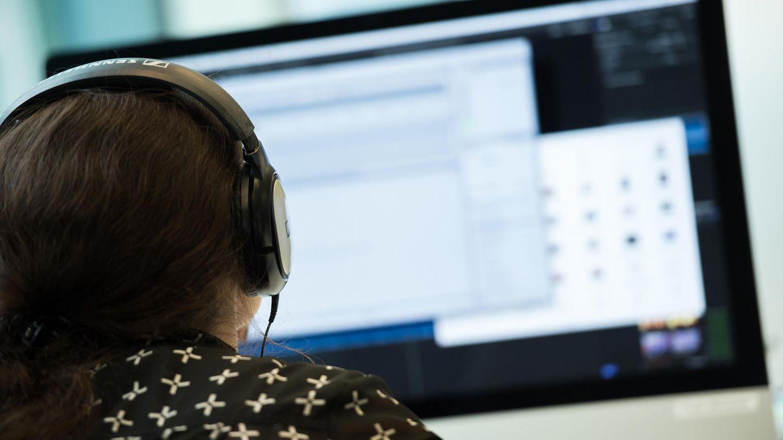 Filesharing: Eine Frau mit Kopfhörern sitzt vor einem Computer.